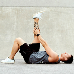man stretching hamstring or thigh muscle after workout